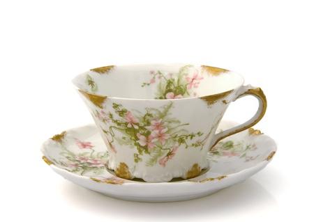 Taza de té de antigüedades y platillo con un estampado de flores aisladas en blanco