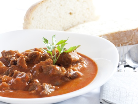goulash: Goulash stew served in white bowl. Bread in the background