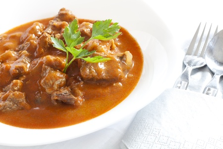 Goulash stew with parsley served in white bowl Stock Photo