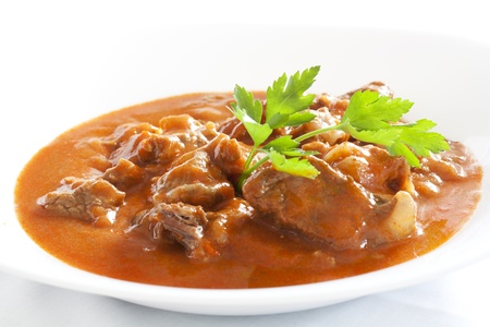 Goulash stew with parsley served in white bowl Imagens