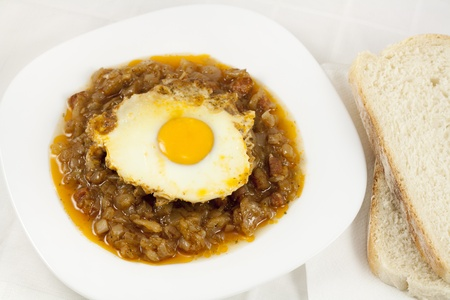 Delicious stew with baked onion, egg and sausages served on table with two slices of bread Stock Photo - 8922578