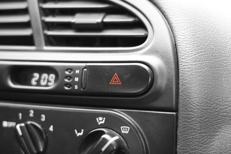 Car emergency lights button on cockpit. Very shallow DOF, focus on triangles on emergency lights button. photo