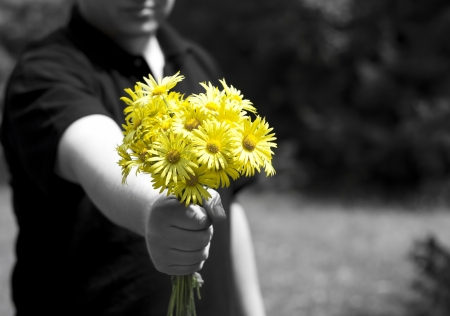 Man giving a present with yellow daisy flowers. Focus on flowers. photo