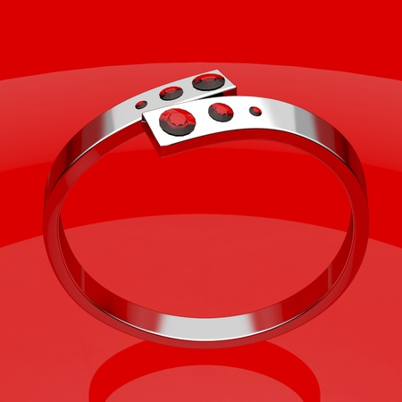 Silver ruby ring on shiny red background photo