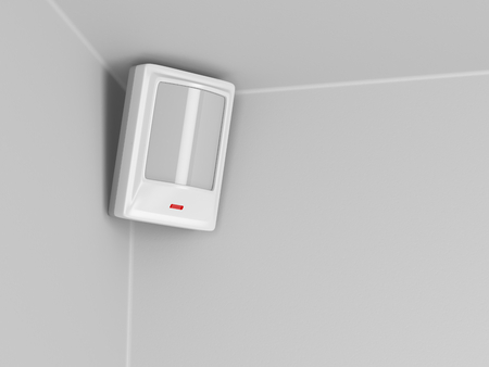 Burglar alarm motion sensor on grey wall photo