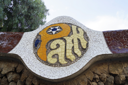 guell: BARCELONA, SPAIN - OCTOBER 08, 2015: Mosaic sign of Park Guell in Barcelona, Spain, designed by famous architect Antoni Gaudi Editorial