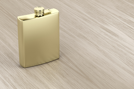 Golden hip flask on wooden table