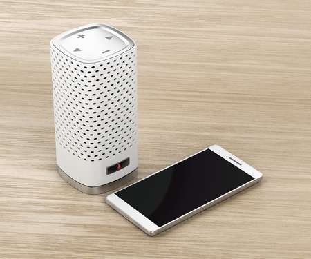 Smart speaker with integrated virtual assistant and smartphone on wood background Stock Photo