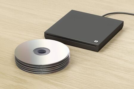 Stack of optical discs and external slot-loading optical drive on wood table Stock Photo
