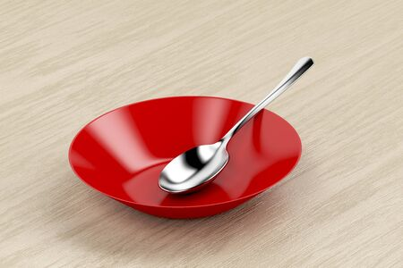 Red empty bowl and silver spoon on wood table