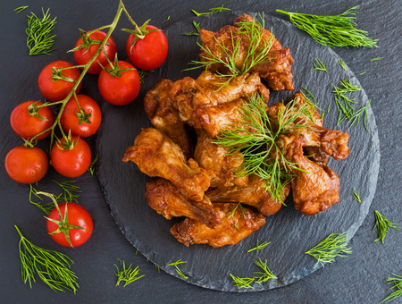 black wings: Chicken wings cooked with barbecue sauce on black stone background. Small cherry tomatoes and dill. Top view.