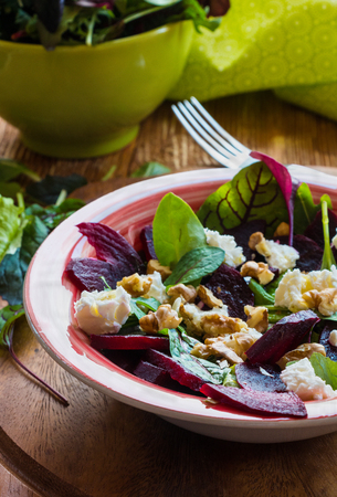 Salad: beet salad with feta cheese and walnuts on wooden background. Top view. 版權商用圖片