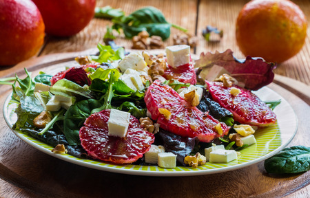 Salad: mix of green salad, feta cheese, red oranges and walnuts. Dressing: olive oil. Selective focus.