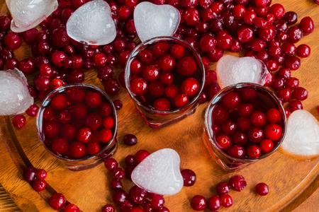 vasos de agua: bebida de arándanos frío en vasos, arándanos y trozos de hielo sobre fondo de madera. Foto de archivo