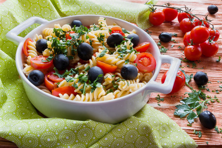 vegeterian: Pasta (fusilli) in white pan on wooden background. Vegeterian, cooked with tomatoes, black olives, garlic and parsley.