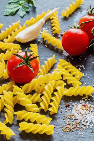 fusilli: Pasta ingredients (fusilli) on black slate background. Stock Photo