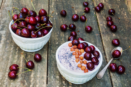 breakfast bowl: Breakfast bowl with yogurt, granola or muesli or oat flakes, fresh cherries and nuts. Ripe berries and retro spoon on old vintage wooden background Stock Photo
