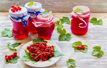 Preserved homemade red currant jam in glass jars on white wooden table. Fresh berries and green leaves, vintage plate.