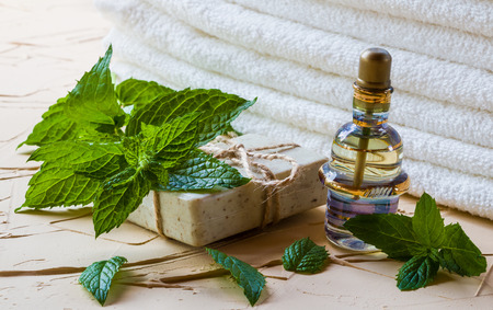 Peppermint essential oil in a glass bottle on a light table. Used in medicine, cosmetics and aromatherapy. White towels, fresh leaves and a piece of soap. Selective focus. Stock Photo