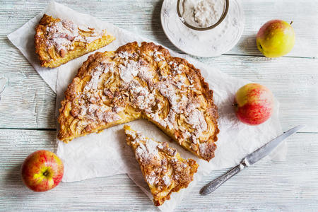 Sliced homemade apple and almond cake on wooden background. Fresh fruits and icing sugar, top view Zdjęcie Seryjne