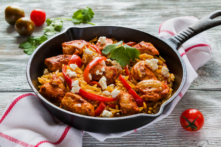 One-pot chicken fillet and orzo pasta with red bell peppers and feta cheese, cooked with garlic, paprika and olive oil. Cast-iron skillet and fresh tomatoes on wooden table. Stock Photo