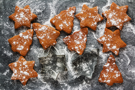 Christmas chocolate  and ginger brown cookies in shape of fir-tree and star on black stone background with powdered sugar, top view. Stock Photo