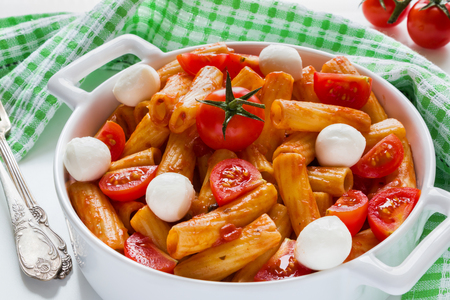 Penne pasta with sauce, mozzarella cheese and cherry tomatoes in casserole on white table. Zdjęcie Seryjne