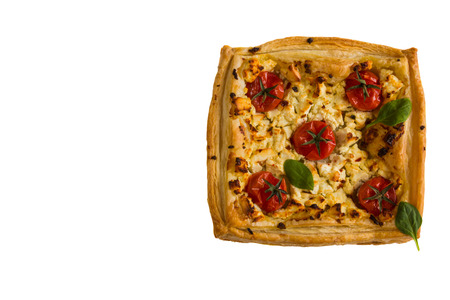 Cherry tomatoes and feta cheese tart made with butter puff pastry. Isolated on white, top view. Zdjęcie Seryjne