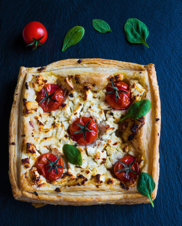 Cherry tomatoes and feta cheese tart made with butter puff pastry. Black stone background, top view.
