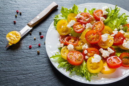 Colorful salad, fresh green leaves and sliced red and yellow cherry tomatoes, white plate, knife, black stone background.