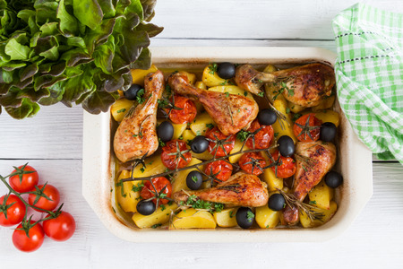 Baked chicken drumsticks in red dish. Cooked with cherry tomatoes, black olives, rosemary and potatoes. White wooden table, top view. Zdjęcie Seryjne