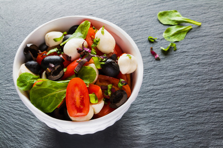 Caprese salad, small mozzarella cheese, fresh green leaves, black olives and cherry tomatoes in white vintage bowl on stone background.