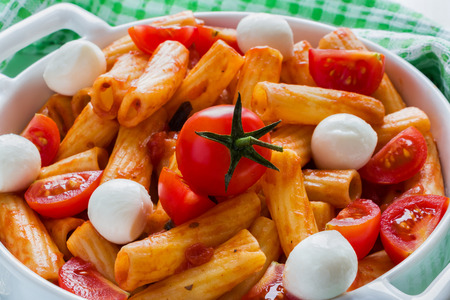 Penne pasta with sauce, mozzarella cheese and cherry tomatoes in casserole on white table. 版權商用圖片