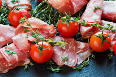 Jamon Serrano sliced with small cherry tomatoes and fresh thyme on black stone background.