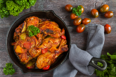 Chakhokhbili, chicken stew, cooked with tomatoes, bell peppers, spices and herbs. Dark wooden background, top view. 版權商用圖片 - 68287473