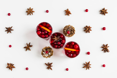 Mulled wine in small glasses with cranberries, anise and oranges. White background, top view.