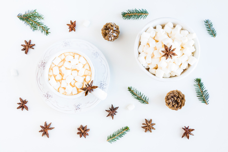 Winter Christmas decoration, fir branches and cones, marshmallows and hot drink, coffee or cacao in a cup. White table, top view, flat lay. Zdjęcie Seryjne