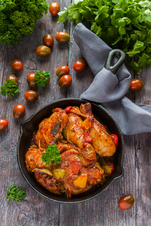 Chakhokhbili, chicken stew, cooked with tomatoes, bell peppers, spices and herbs. Dark wooden background, top view. Zdjęcie Seryjne