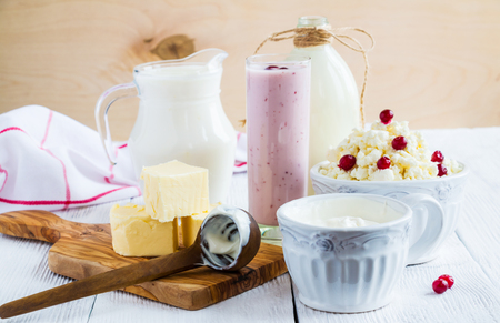 produces: Dairy produce. Milk in bottle, cottage cheese in bowl, kefir in jar, cranberry yogurt in glass, butter and fresh berries. Wooden white table. Stock Photo