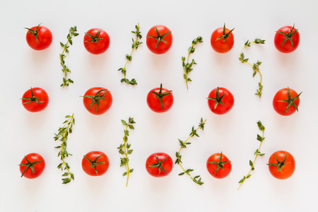 Small red cherry tomatoes and fresh green thyme leaves on white table. Flat lay, top view.