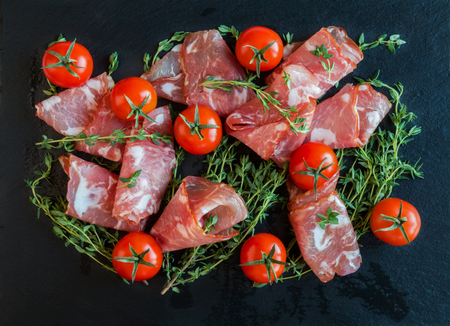 Jamon Serrano sliced with small cherry tomatoes and fresh thyme on black stone background. Top view.