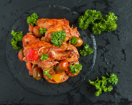 Chakhokhbili, chicken stew, cooked with tomatoes, bell peppers, spices and herbs. Black stone background, top view. Zdjęcie Seryjne