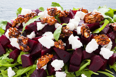 Dietary salad of beets, arugula, feta cheese and caramelized walnuts with olive oil and lemon juice. Black stone background.