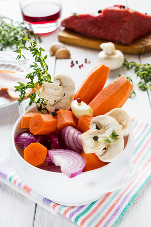 Ingredients for Boeuf Bourguignon, carrot, onion, mushrooms, bacon, wine, beef, garlic, thyme. White bowl, wooden table.