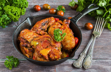 Chakhokhbili, chicken stew, cooked with tomatoes, bell peppers, spices and herbs. Dark wooden background.