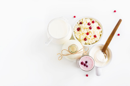 Dairy produce. Milk in bottle, cottage cheese in bowl, kefir in jar, cranberry yogurt in glass, butter and fresh berries. White table, top view. Zdjęcie Seryjne