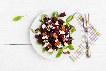 Dietary salad of beets, arugula, feta cheese and caramelized walnuts with olive oil and lemon juice. White wooden table, top view.