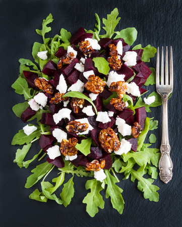 Dietary salad of beets, arugula, feta cheese and caramelized walnuts with olive oil and lemon juice. Black stone background, top view. Zdjęcie Seryjne