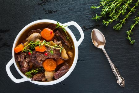 Carne de vaca Bourguignon en un cuenco de sopa blanco en el fondo de piedra negro, visión superior. Guisar con zanahorias, cebollas, champiñones, tocino, ajo y bouquet garni. El plato se sirve con tomillo fresco.