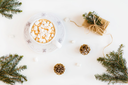 Winter Christmas decoration, fir branches and cones, wrapped gift, marshmallows and hot drink, coffee or cacao in a cup. White table, top view, flat lay.